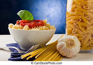Pasta with tomato sauce on blue background - photo of...