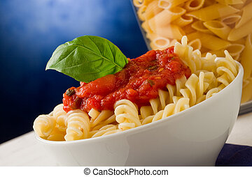 Pasta with tomato sauce and basil on blue background - photo...