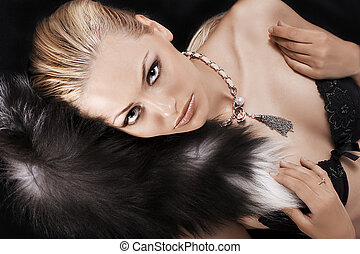 sexy blonde laying on black just wearing fur