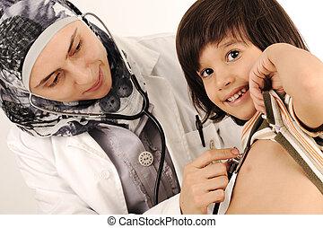 Muslim female doctor in hospital examining a little boy