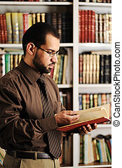 Young man reading book in library