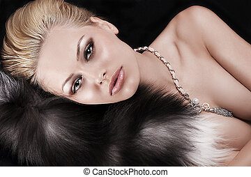 blonde with up-do laying on black - sexy blonde model posing...