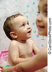 Adorable baby boy taking a bath with soap suds on hair