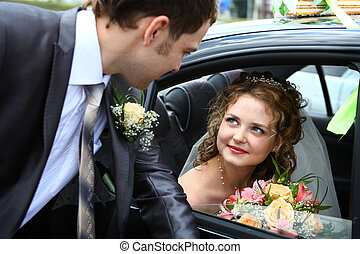 Bride in car and groom looking on her