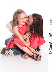 Kiss on cheek a mothers love to young daughter