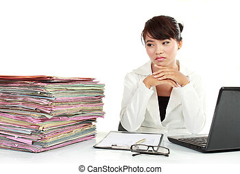 young business woman with laptop and many paper stressed at...