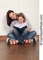 Mother teaching daughter to read home education