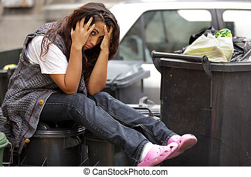 young poor girl in bin - young poor girl very sad sitting on...
