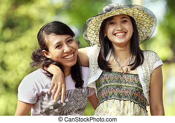 multi ethnic friend smiling outdoor - two young multi ethnic...