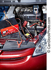 Auto repair. - Battery charger and car in auto repair shop.