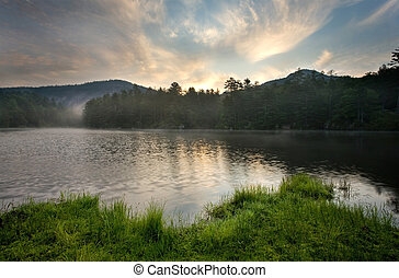 Sunrise over Mountain Lake - Fog evaporates from a lake at...