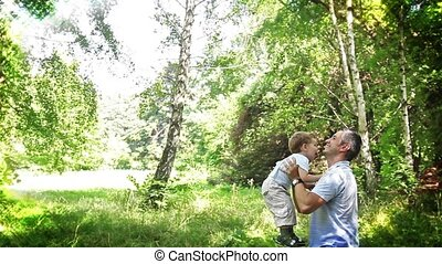 Adorable Boy and Father in Park
