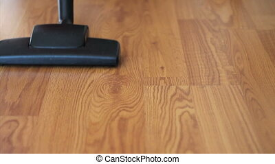 Vacuuming Laminate Floor-Close Up - A housewife uses a...