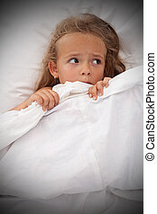 Little girl in bed awaken by nightmares laying scared