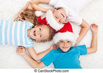 Happy kids at christmas time laying on the floor in circle