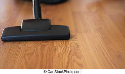 Vacuuming Laminate Flooring - A housewife uses a vacuum to...