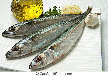 mackerel fish with ingredients on white dish