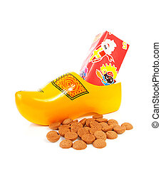 Dutch wooden shoe with presents and pepernoten over white...