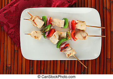Checken Kabobs on White Plate - cubed chicken kabobs with...