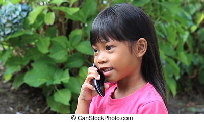 Little Girl Talking On Cell Phone - A cute little Asian girl...