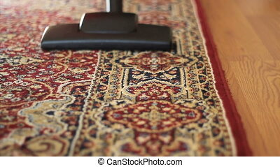 Vacuuming Colorful Carpet - A housewife uses a vacuum to...