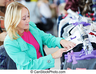 Young woman at shop - Young woman in colorful raincoat...