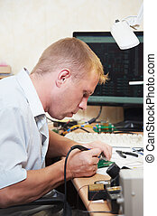 worker soldering microchip scheme - mechanical technician...