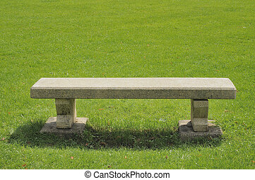 stone bench on green field - summer shot of a stone bench on...