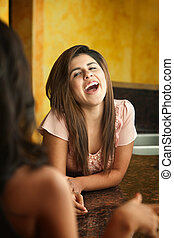 Young Woman Laughs - Hispanic girl with friend laughs out...