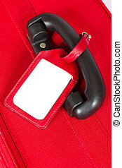 Red suitcase with blank identification tag over white. Closeup.
