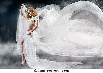 Beautiful woman walking with flying white chiffon fabric, waving  as wings on a wind flow. Mysterious fantasy background