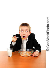 schoolboy eating corn flakes isolated on the white