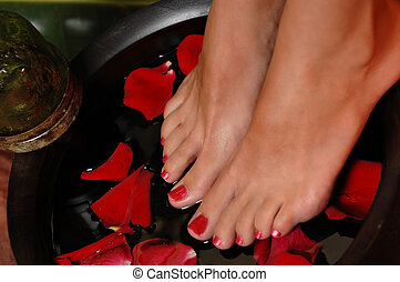 Spa Pedicure - Close up of a woman's feet on a rose petal...