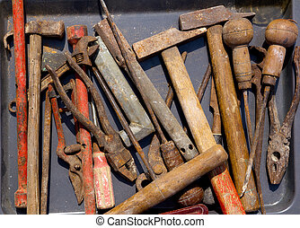 aged weathered rusty hand tools in black iron tray