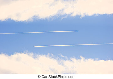 Airplane vapour contrails against vivid blue sky - White...