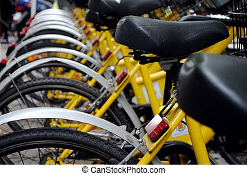 parked yellow bicycles, concept of bike sharing