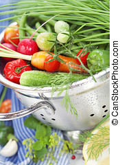 Fresh vegetables in metal colander with blue napkin