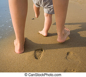 Mother and child walking on a sandy beach - mom helps to...
