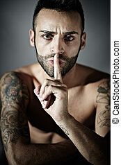 tattooed man with finger on mouth - portrait of proud young...