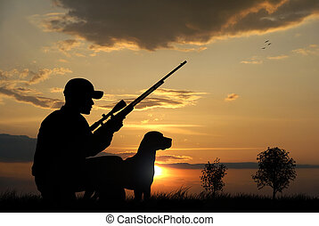 Hunter - Hunter with his dog silhouettes on sunset...