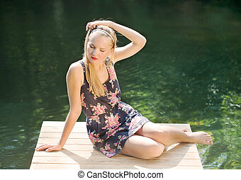 beautiful girl with long hair has a rest at water
