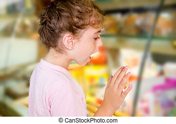 child little girl looking in food shop display excited with...