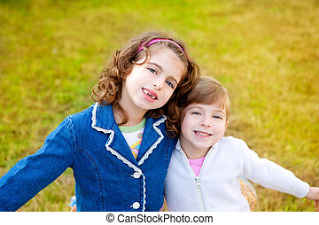 happy sister girls in winter park grass playing