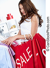 Spree - Young woman buying things at sales period