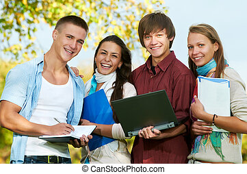 Group of smiling young students outdoors - Group portrait of...