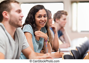 Smiling students listening a lecturer in an amphitheater