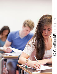 Portrait of students having a test in a classroom