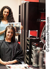 Portrait of a hairdresser showing to her customer her new haircut with a mirror