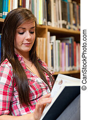 Portrait of a smiling female student reading
