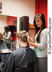 Portrait of a focused woman cutting a man's hair with...